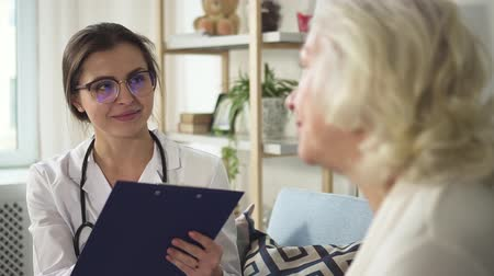 Young female doctor in uniform and glasses is making noted and talking with patient. Healthcare center for illness consulting, professional medical appointment and clinic practitioner of neurologist service. Stock Footage