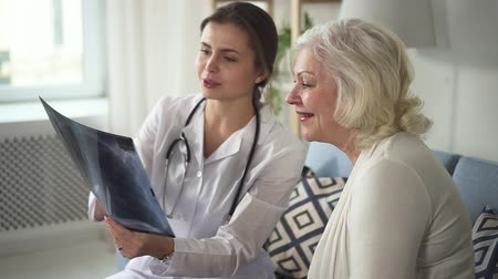 Qualified and experienced specialist with stethoscope on neck looking and discuss X-rays picture with old retired lady. They sitting inside bright living room and smiling