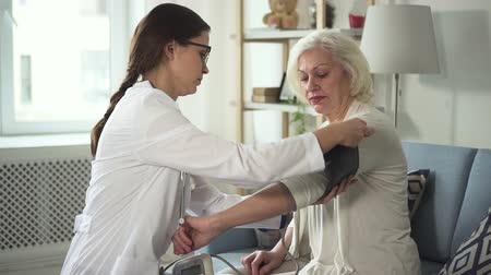 nadciśnienie : Old lady called young and professional practitioner wearing in white coat at home. She use an instrument to measure pressure while they sitting on soft couch or sofa in room with modern interior