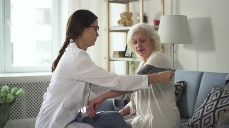Confident and focused practitioner wearing in white medical coat came at home visit retired woman. She puts pressure gauge on patient hand while sitting on soft couch or sofa in room