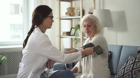 Professional young doctor assistant wearing in white coat uniform visit old lady patient in her cozy and charming flat with bright light room. Nurse measuring blood pressure using special equipment