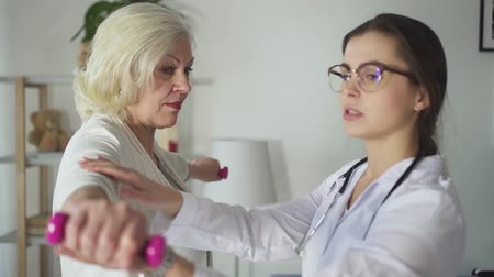 Beautiful doctor in white uniform is helping to aged woman exercising right way. Mature  american patient is standing and training for good endurance, physical health, leisure activity. Private support and assistance. Stock Footage
