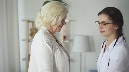 Successful young doctor wearing in white coat visit mature patient woman in her bright house with modern interior room. Practitioner making training exercise with old lady and using dumbbell