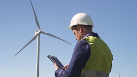 Adult or mature specialist workman in protective white helmet and standing with portable tablet in hands against windfarm power station on landscape with blue sky. Male making inspections of objects