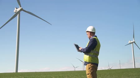 Adult or mature maintenance man in special uniform and hardware standing with modern digital tablet against windmill power station on beautiful landscape. Male entering information into program Stock Footage