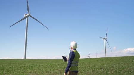 Adult or mature collar worker in hardhat helmet and special clothes standing with digital tablet in hands against wind mill power station on background with blue sky. Male using program on device