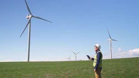 Adult or mature specialist man in protective uniform wear standing with portable tablet in hands against landscape wind turbine power station on background. Male checking information on device