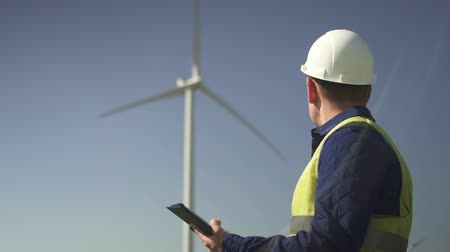 Adult or mature professional man in white hard hat and green uniform wear standing with modern digital tablet against windmill power station on beautiful landscape. Male making inspections of objects