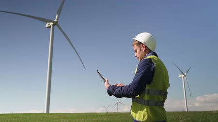 Adult or mature maintenance man standing with digital tablet in hands against windfarm power station on landscape with blue sky. Male entering information into special online program Stock Footage