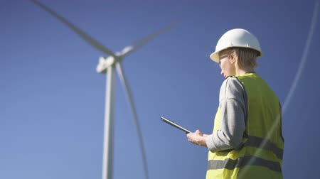 Adult or mature collar worker in white hard hat and green uniform wear standing with modern tablet against wind farm power station on beautiful landscape. Female using program on device