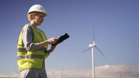 Adult or mature professional woman in special uniform clothes standing with tablet or computer in hands against windmill power station on beautiful landscape. Female making inspections of objects