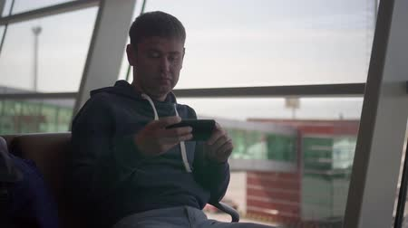 American male man sits in airport in panorman window an chair and looks app in phone, in order to check the gate.background a panorman window with buildings