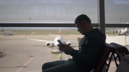 elfog : American man sits in an airport in an armchair and looks at a ticket, with the goal of checking the gate, in the background there is a panorman window with an airplane ready for service