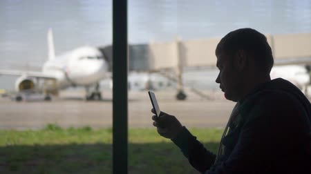 businessman using phone at the airport. silhouette of a man traveler. business and travel Stock Footage