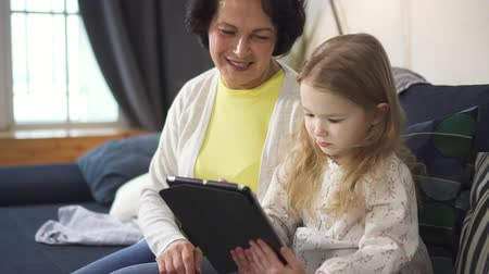 Mother is showing charming little girl laptop and control screen of tablet. Daughter is smiling and laughing with woman together by gaming and using new modern connected technology. Family in slow motion. Stock Footage