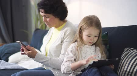 Senior woman is sitting on sofa and looking at smartphone while young girl is watching something interesting on tablet. Granddaughter is playing using modern technology laptop. Retired grandmother is serious and concentrated on phone.