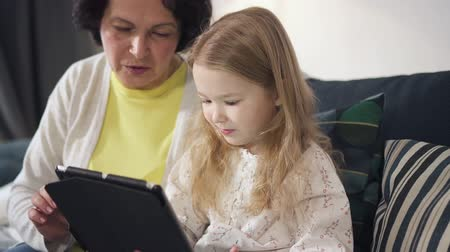 Mother is sitting on sofa, talking and showing to daughter the best using of laptop. Little girl is learning in printing on modern new tablet online enjoying the whole process. Cheerful female is smiling.