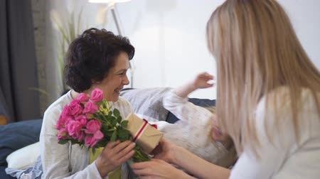 holidays : Happy senior grandparent is getting present and lovely rose flower bouquet from daughter and female grandchild. All women are laughing and looking so happy together. Retired smiling grandmother love family. Stock Footage
