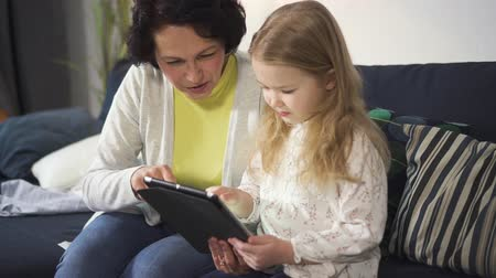 Adult woman is sitting on sofa and teaching little girl using new digital technology. Granddaughter is holding laptop and enjoying indoor watching video together. Family relationship and love in smiling lifestyle. Stock Footage