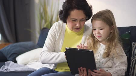 bond : Little girl is showing to senior woman new fun cyber game on tablet. Young female gamer is sitting on sofa with grandmother and watching at computer display. Virtual play media industry and futuristic generation.