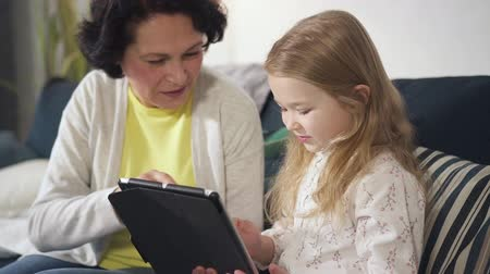 área de trabalho : Little cheerful attractive girl is sitting and using touchscreen keyboard for elementary lesson and onlive education by typing diverse information at home. Family connection and parent child relations.