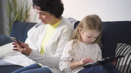 Woman is sitting on sofa and touching phone screen while child using laptop for playing or computing at home. Digital wireless electronic devices for network and game. Mother and daughter is working together. Stock Footage