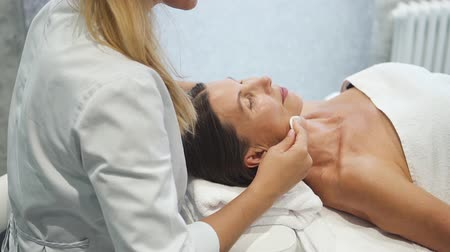 Adult woman is lying on massage table and getting face healthcare treatment therapy.Beautiful doctor is doing skincare medical procedure for wellbeing of brunette beauty. Professional cosmetologist technology.