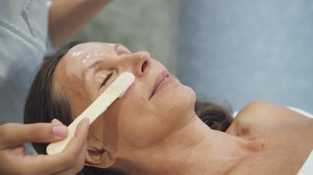 чувствительный : Dermatologist applying rejuvenating mask to retired female face. Senior woman lying on massage table, relaxing, enjoing skincare procedures in cosmetology center.