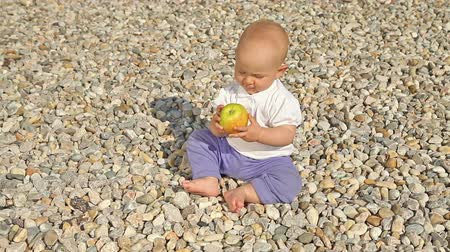 munch : Baby playing awith an apple on pebbles background