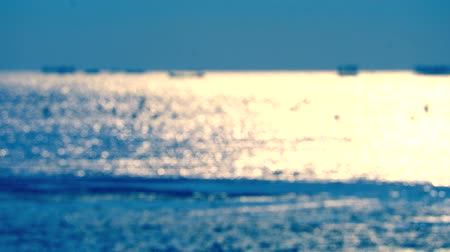 refletindo : blur reflection sun light on sea and little wave slow motion