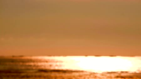 refletir : blur reflection orange color of sun light on sea surface and little wave moving