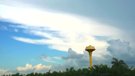 preservação : yellow water tank and cloud moving over green coconut garden time lapse