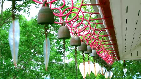 knocking : Bells hanging in a row by the wind roof of temple Stock Footage
