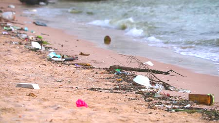 litter box : sunset on sea with plastic and waste on the beach and the waves blew them into sea Stock Footage