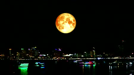 perigee : blood moon over colorful of night city and light of boat on sea