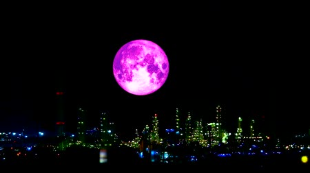 blood moon : pink harvest moon moving pass light oil refinery and dark night sky Stock Footage