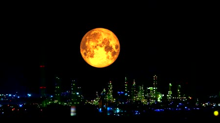 blood moon : blood harvest moon moving pass light oil refinery and dark night sky