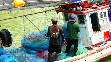 coletando : Fishermen collecting nets after fishing in the morning