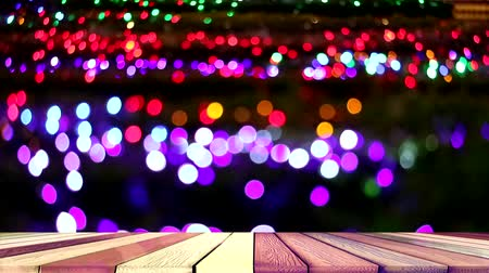 pretpark : wood top table and blur purple red rainbow color light on tree in the night garden Stockvideo