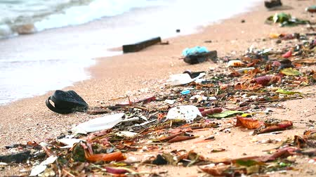 poluir : sunset on beach with plastic rubber and waste are left on beach and waves blew them into the sea