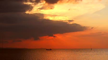 fly fishing : red sunset on water surface of sea and dark red cloud on sky