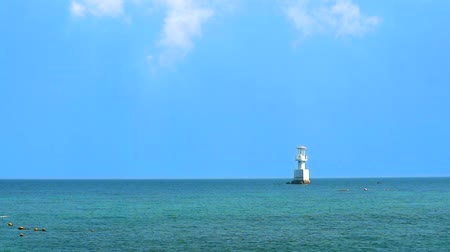 boa : white cloud and lighthouse is surrounded by coral reefs in the sea and blue sky
