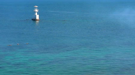 befőz : white lighthouse is surrounded by coral reefs in blue green sea Stock mozgókép