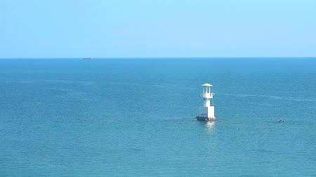 marine park : white lighthouse is surrounded by coral reefs in the sea and clear sky