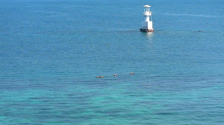 befőz : white lighthouse is surrounded by coral reefs in the blue green sea