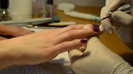 glove : Manicurist paints your nails painted purple Stock Footage