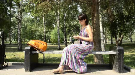 feminity : young pregnant woman in the park gets a credit card Stock Footage