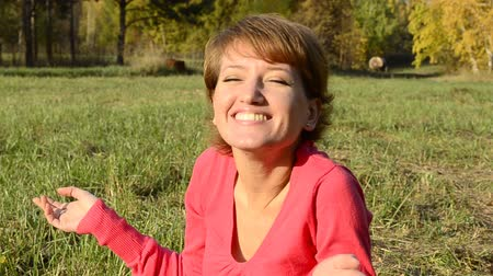jungle : A young woman in a red sweater smiling sitting in autumn park