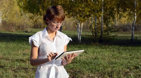 ler : Young woman running on a Tablet PC in the autumn park