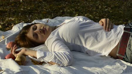 beautiful day : Young woman lying on bedspread in autumn park Stock Footage
